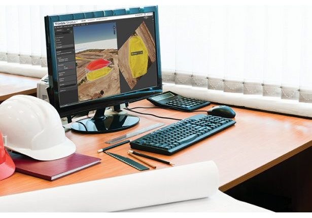 Working place with computer, hard hat and project drawings. Draw